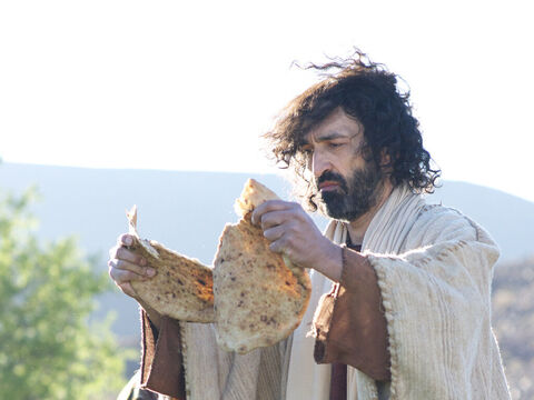 After instructing the crowd to sit down on the ground, Jesus took the seven loaves and the fish, and after giving thanks, He broke them in pieces. – Slide 7