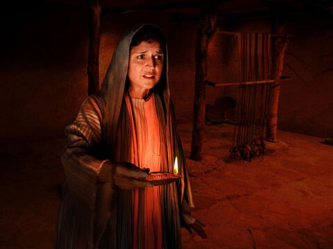 She lights an oil lamp and searches inside her house. – Slide 9