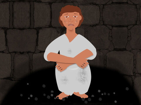 Joseph was put in an empty well and felt very sad and afraid. As he sat in the darkness he could hear his brothers above him talking and eating. He cried for help but they ignored him. They had taken his coat of many colours. – Slide 6