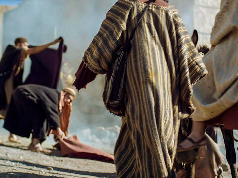 Many people spread their cloaks on the ground for Jesus to ride over while others spread branches they had cut in the fields. – Slide 9